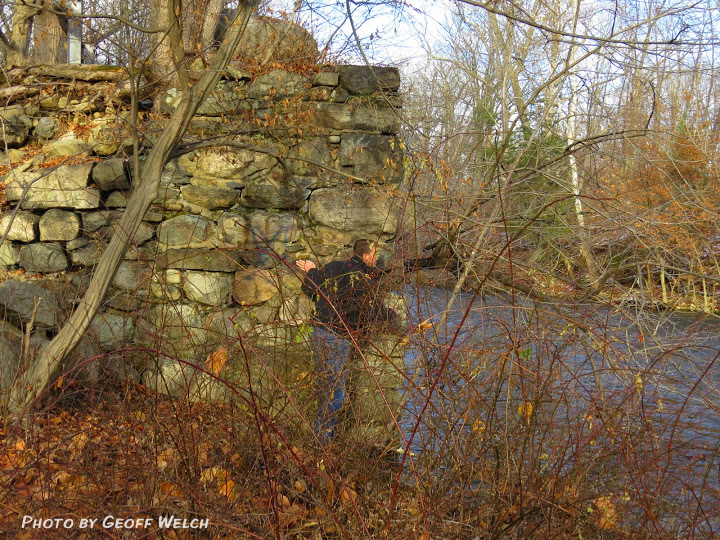 Ed Marse peeks around the remains of Brown's Bridge, which at one time spanned the Ramapo River in Sloatsburg, leading to Cappamore Farms.